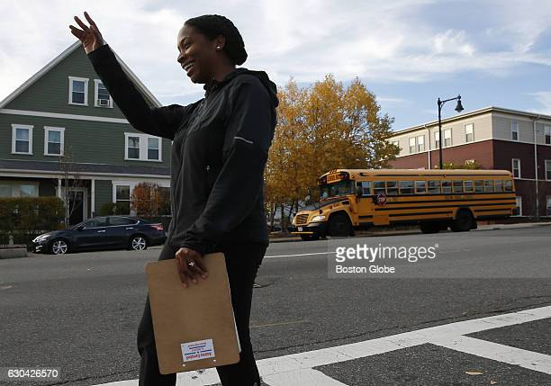 Andrea Joy Cambell running for Boston City Council waves to pedestrians as she knocks on doors during the last day of campaigning in Roslindale MA on...