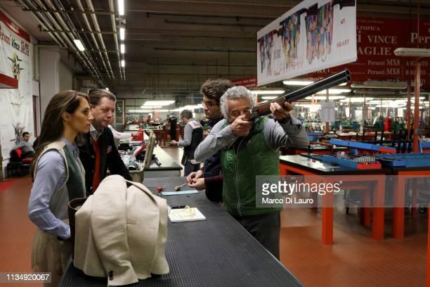 Andrea Maria Neira a 29yearold Spanish client of Perazzi observes Mauro Perazzi taking aim with a shotgun while Mauro's son Nicola Perazzi talks with...