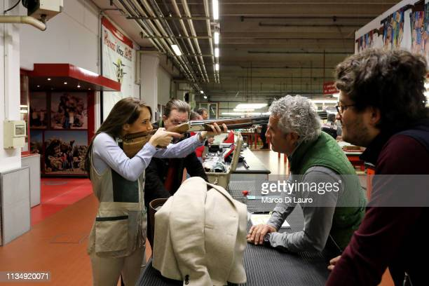 Andrea Maria Neira a 29yearold Spanish client of Perazzi takes aim with a rifle in front of Mauro and Nicola Perazzi next to Staffan Schullstrom...