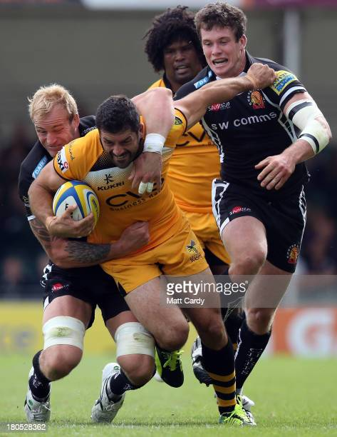 Andrea Masi of London Wasps is tackled by Damien Welch and Ian Whitten of Exeter Chiefs during the Aviva Premiership match between Exeter Chiefs and...
