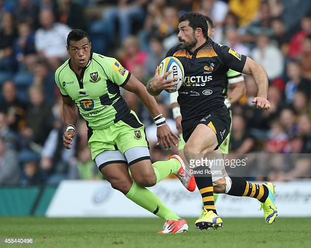 Andrea Masi of Wasps breaks with the ball away from Luther Burrell during the Aviva Premiership match between Wasps and Northampton Saints at Adams...