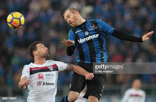 Andrea Masiello of Atalanta BC jumps for the ball against Artur Ionita of Cagliari Calcio during the serie A match between Atalanta BC and Cagliari...