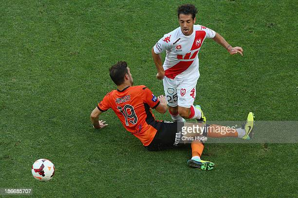 Andrea Migliorini of the Heart trips over Jack Hingert of the Roar during the round four ALeague match between Brisbane Roar and the Melbourne Heart...