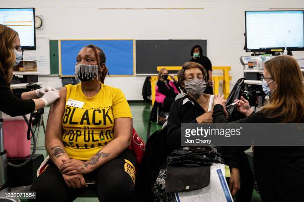 Andrea Moore sits as her mother, Alma Penn receives her COVID-19 vaccine in the gymnasium at Whitney M. Young Elementary School on April 2, 2021 in...