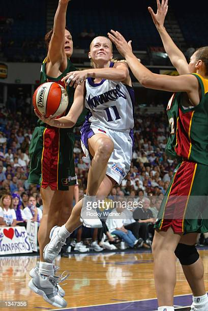 Andrea Nagy of the Sacramento Monarchs goes to the basket under pressure from Kamila Vodichkova and Adia Barnes of the Seattle Storm during a game on...
