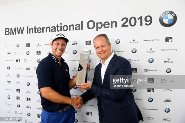 Andrea Pavan of Italy receives the trophy from Tourrnament President and BMW representative Sebastian Mackensen after his victory during a playoff...
