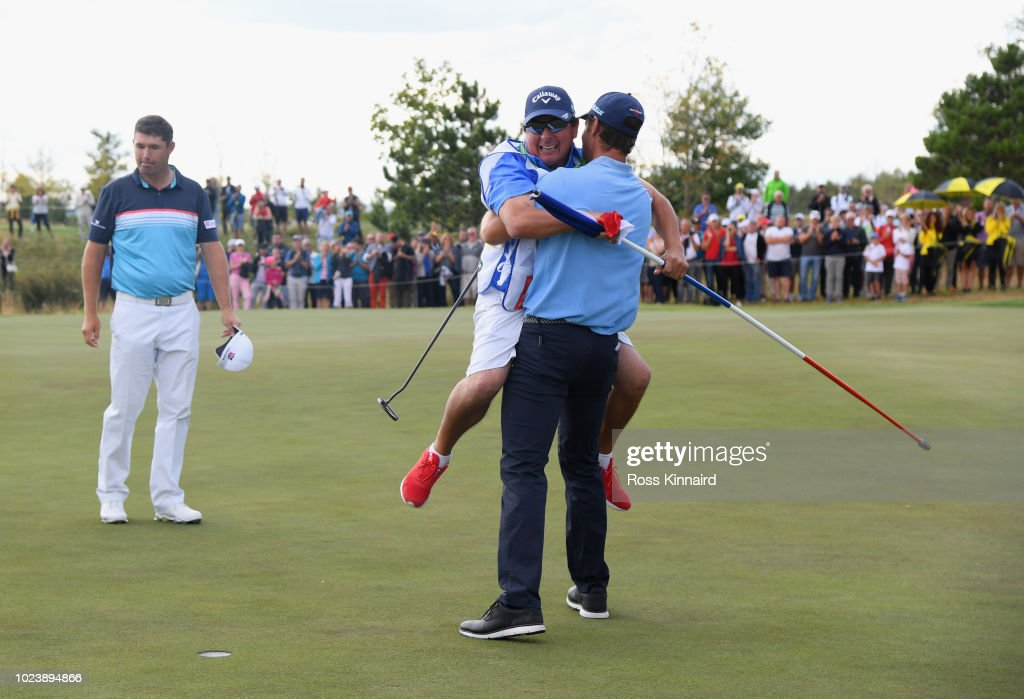 Andrea Pavan of Italy victory with his caddie on the 18th green as Padraig Harrington of Ireland look son during day four and final round of the the D+D REAL Czech Masters at Albatross Golf Resort on August 26, 2018 in Prague, Czech Republic.