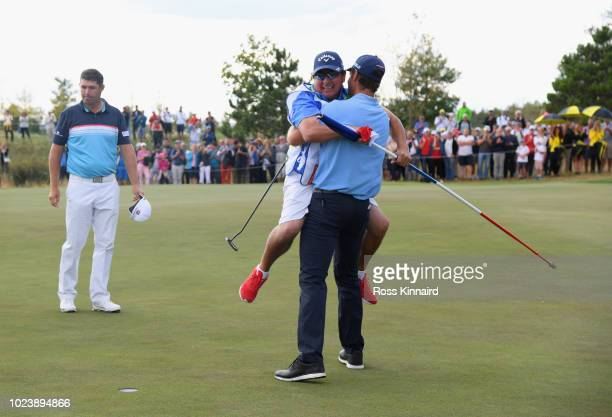 Andrea Pavan of Italy victory with his caddie on the 18th green as Padraig Harrington of Ireland look son during day four and final round of the the...
