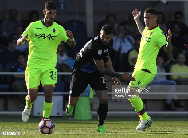 Andrea Petagna of Atalanta BC is challenged by Adam Masina and Federico Viviani of Bologna FC during the Serie A match between Atalanta BC and...