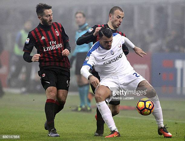 Andrea Petagna of Atalanta BC is challenged by Luca Antonelli and Andrea Bertolacci of AC Milan during the Serie A match between AC Milan and...