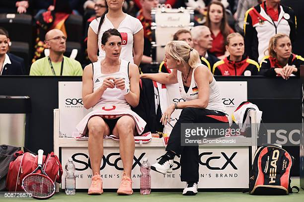 Andrea Petkovic of Germany looks on as she gets instructed by team captain Barbara Rittner during her match against Belinda Bencic of Switzerland...