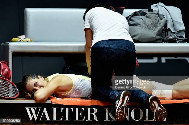 Andrea Petkovic of Germany receives medical treatment after falling during her match against Agnieszka Radwanska of Poland during Day 4 of the...