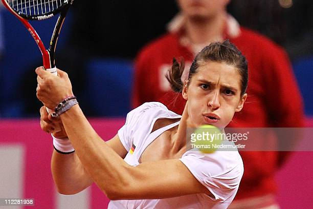Andrea Petkovic of Germany returns the ball to Melanie Oudin of USA during the second day of the Fed Cup match between Germany and United States at...