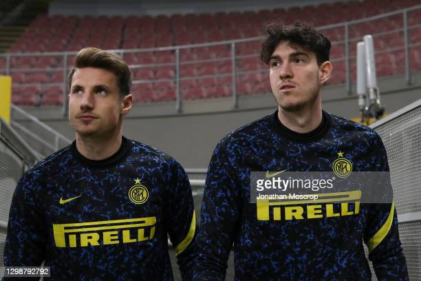 Andrea Pinamonti and Alessandro Bastoni of Internazionale enter the field of play for the warm up prior to the Coppa Italia match between FC...