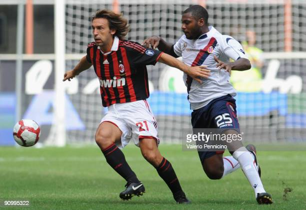 Andrea Pirlo of AC Milan battles for the ball with Marcelo Zalayeta of Bologna FC during the Serie A match between AC Milan and Bologna FC at Stadio...