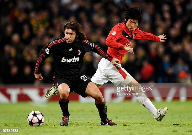Andrea Pirlo of AC Milan is challenged by JiSung Park of Manchester United during the UEFA Champions League First Knockout Round second leg match...