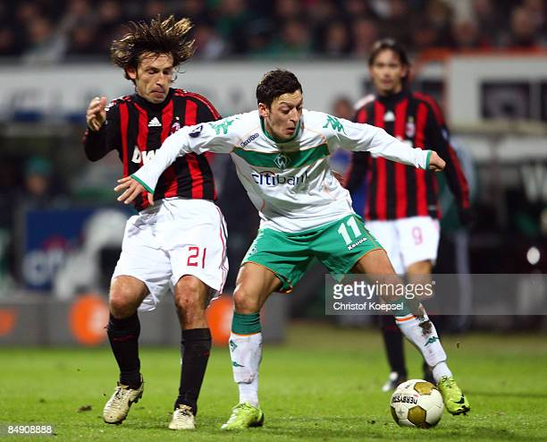 Andrea Pirlo of AC Milan tackles Mesut Oezil of Bremen during the UEFA Cup Round of 32 first leg match between Werder Bremen and AC Milan at the...