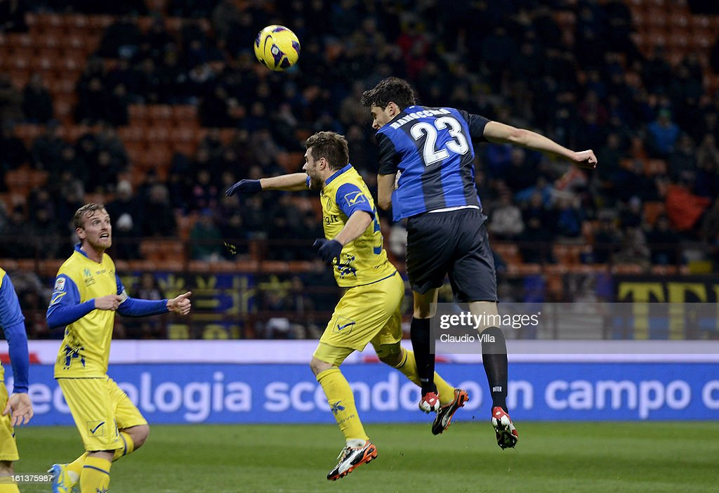 Andrea Ranocchia of Inter Milan (R) heads the ball to score his team's second goal during the Serie A match between FC Internazionale Milano and AC Chievo Verona at San Siro Stadium on February 10, 2013 in Milan, Italy.