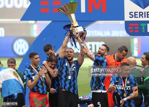 Andrea Ranocchia of Internazaionale embraces Head coach Antonio Conte as team mates Danilo D'Ambrosio and Roberto Gagliardini celebrate with Scudetto...