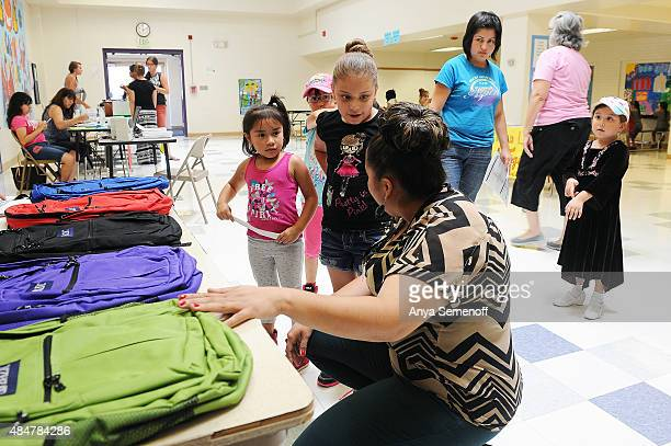 Andrea Renteria the assistant principal at Garden Place Academy helps Alicia Valenzuela center and her cousin Danna Valenzuela left pick out what...