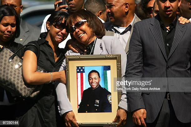 Andrea Reyes weeps as she holds a photo of her deceased son Police Officer Alexander Felix during funeral at Our Lady of Lourdes Church at 463 west...