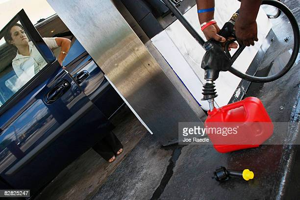 Andrea Rincon waits as she pumps gas into her vehicle as another customer puts gasoline into a container September 15 2008 in Miami Florida Gasoline...