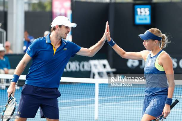 Andrea Sestini Hlavackova of the Czech Republic and Edouard RogerVasselin of France talk tactics in their first round mixed doubles match against...