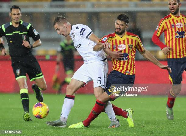 Andrea Tabanelli of Lecce competes for the ball with Marko Rog of Cagliari during the Serie A match between US Lecce and Cagliari Calcio at Stadio...
