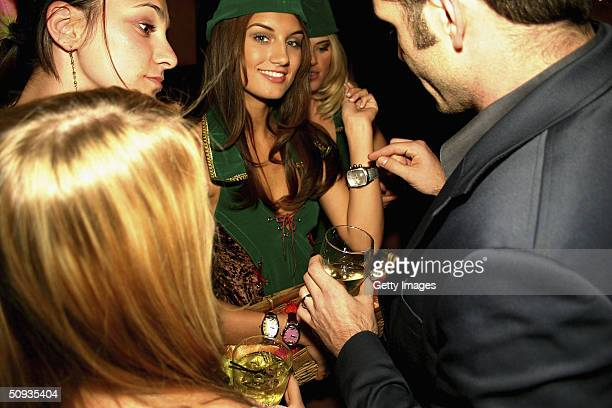 Andrea Tiede smiles as her Invicta watch is looked at by partygoers on June 5 2004 in Las Vegas Nevada