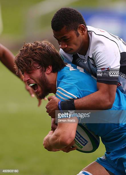Andrea Trotta of Italy is tackled during the 2014 Junior World Championship match between Fiji and Italy at QBE Stadium Auckland on June 20 2014 in...