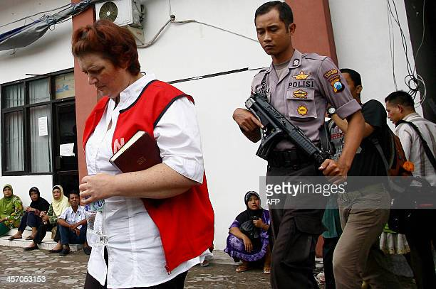 Andrea Waldeck is guarded by an Indonesian policeman prior to her trial at a court in Surabaya on December 16 2013 An Indonesian prosecutor on...