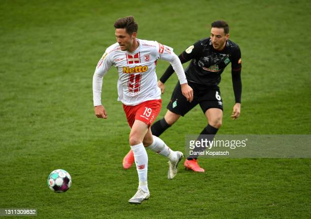 Andreas Albers of Jahn Regensburg battles for possession with Kevin Moehwald of SV Werder Bremen during the DFB Cup quarter final match between Jahn...