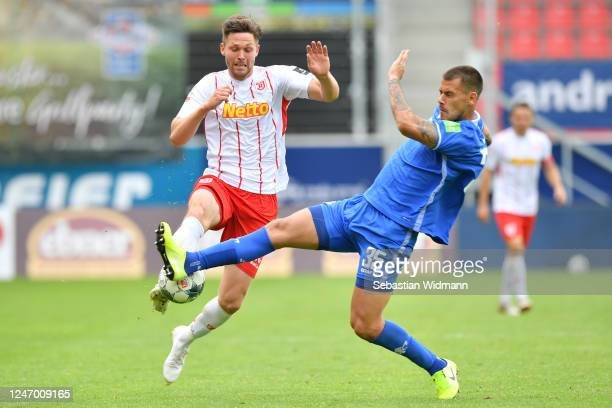 Andreas Albers of Regensburg is challenged by Dario Dumic of Darmstadt during the Second Bundesliga match between SSV Jahn Regensburg and SV...