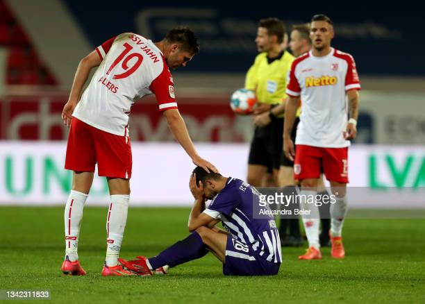 Andreas Albers of SSV Jahn Regensburg touches dejected Soufiane Messeguem of FC Erzgebirge Aue after Aue's 3-2 loss of the Second Bundesliga match...