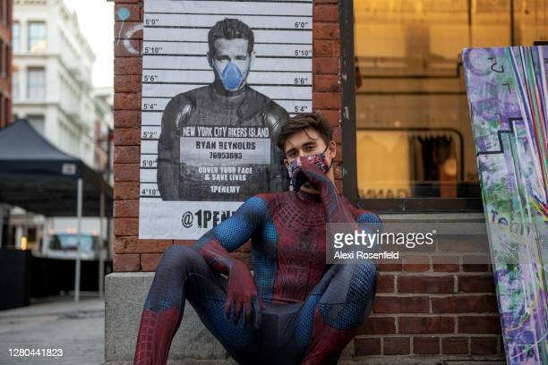 """Andreas Alfaro, dressed in a Spider-Man costume, poses near a poster of Ryan Reynolds that reads, """"cover your face and save lives"""" on October 15,..."""
