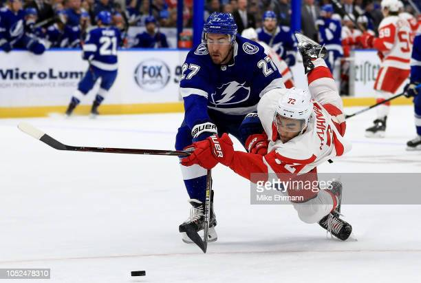 Andreas Athanasiou of the Detroit Red Wings and Ryan McDonagh of the Tampa Bay Lightning fight for the puck during a game at Amalie Arena on October...