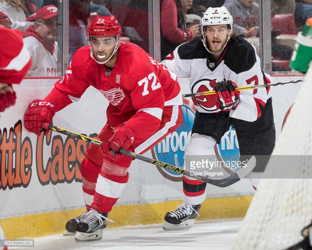 Andreas Athanasiou of the Detroit Red Wings battles along the boards behind the net with Jon Merrill of the New Jersey Devils during an NHL game at...