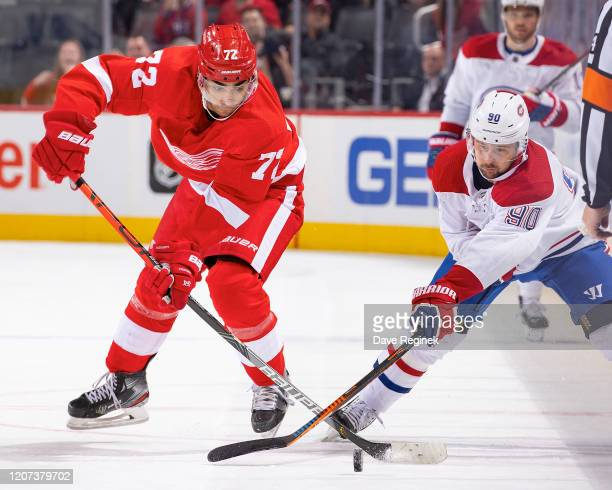 Andreas Athanasiou of the Detroit Red Wings battles for the puck with Tomas Tatar of the Montreal Canadiens during an NHL game at Little Caesars...