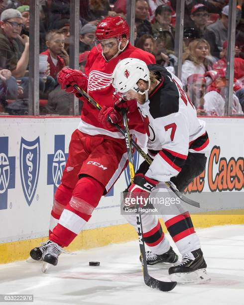Andreas Athanasiou of the Detroit Red Wings battles for the puck with Jon Merrill of the New Jersey Devils during an NHL game at Joe Louis Arena on...