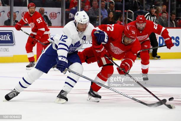 Andreas Athanasiou of the Detroit Red Wings battles with Patrick Marleau of the Toronto Maple Leafs for the puck during the third period at Little...