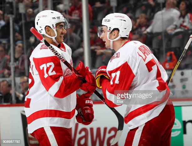 Andreas Athanasiou of the Detroit Red Wings congratulates Dylan Larkin after Larkin scored in the third period against the New Jersey Devils on...