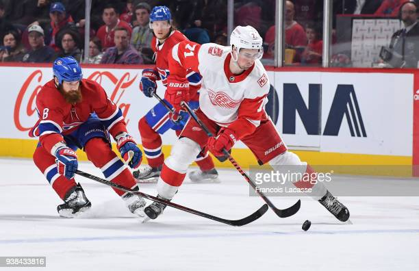 Andreas Athanasiou of the Detroit Red Wings controls the puck while being challenged by Jordie Benn of the Montreal Canadiens in the NHL game at the...