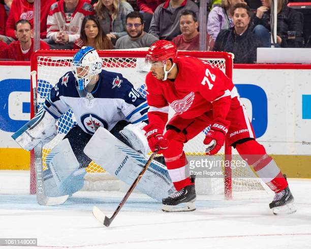 Andreas Athanasiou of the Detroit Red Wings follows the play next to Laurent Brossoit of the Winnipeg Jets during an NHL game at Little Caesars Arena...