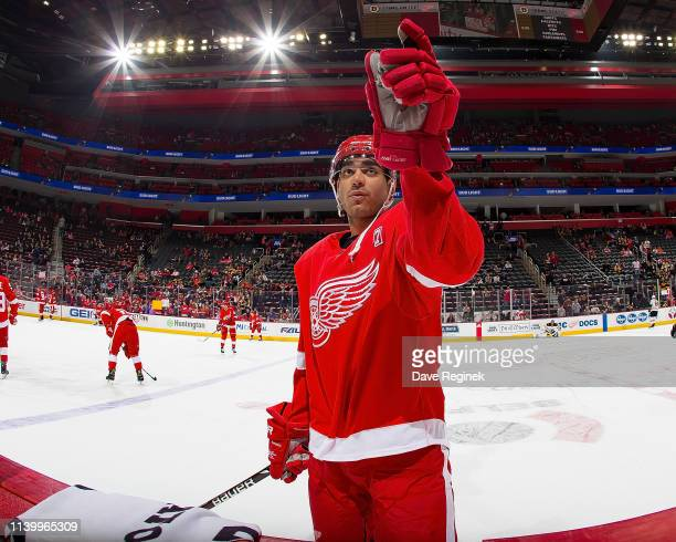 Andreas Athanasiou of the Detroit Red Wings gets ready to toss a puck into the stands during warmups prior to an NHL game against the Boston Bruins...