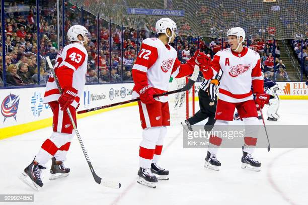 Andreas Athanasiou of the Detroit Red Wings is congratulated by Justin Abdelkader of the Detroit Red Wings and Darren Helm of the Detroit Red Wings...