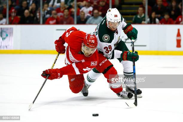 Andreas Athanasiou of the Detroit Red Wings is knocked off the puck by Nate Prosser of the Minnesota Wild during the second period at Joe Louis Arena...
