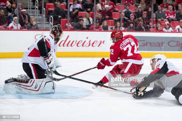Andreas Athanasiou of the Detroit Red Wings is tripped by Dion Phaneuf of the Ottawa Senators on a break away shot on goaltender Craig Anderson of...