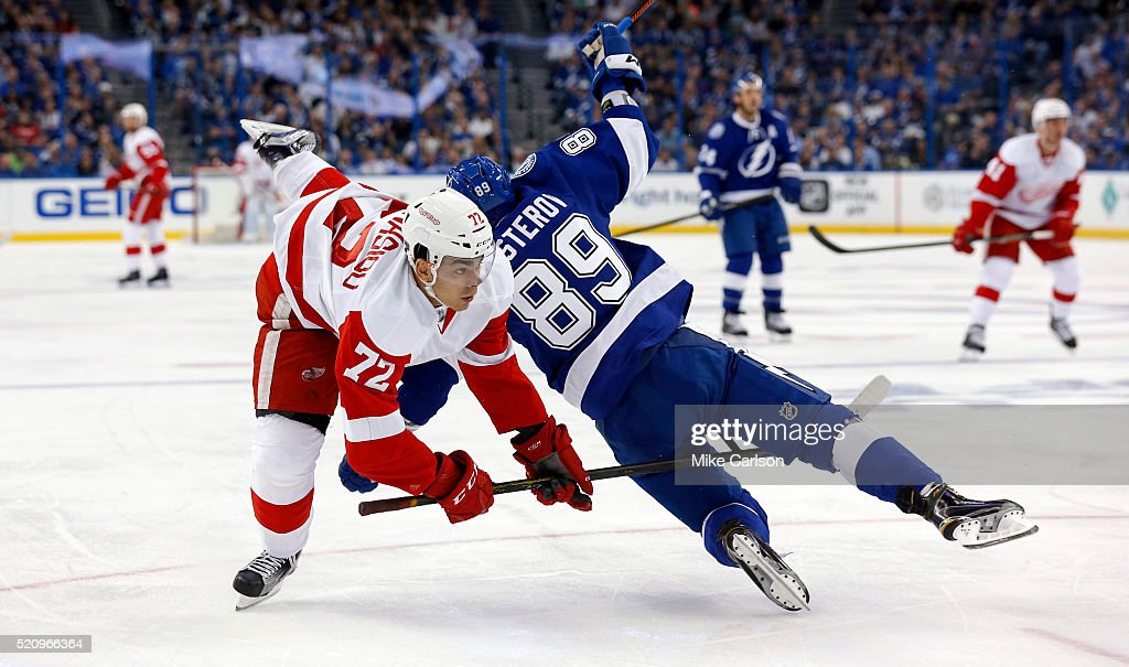 Andreas Athanasiou #72 of the Detroit Red Wings is upended by Nikita Nesterov #89 of the Tampa Bay Lightning during the first period in Game One of the Eastern Conference Quarterfinals during the 2016 NHL Stanley Cup Playoffs at Amalie Arena on April 13, 2016 in Tampa, Florida.