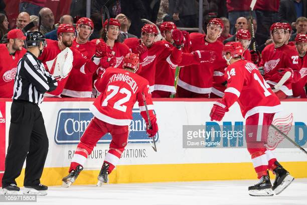 Andreas Athanasiou of the Detroit Red Wings pounds gloves with teammates on the bench following his third period goal during an NHL game against the...