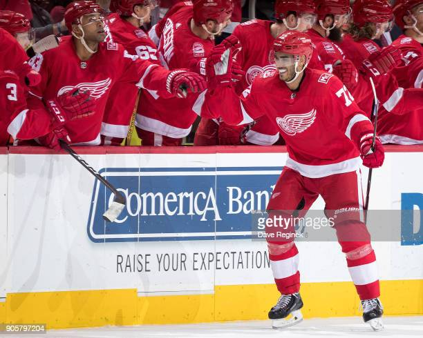 Andreas Athanasiou of the Detroit Red Wings pounds gloves with teammates on the bench following his second period goal during an NHL game against the...